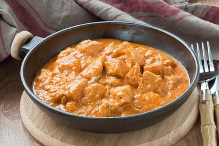 Chicken with curry sauce in frying pan on wooden background