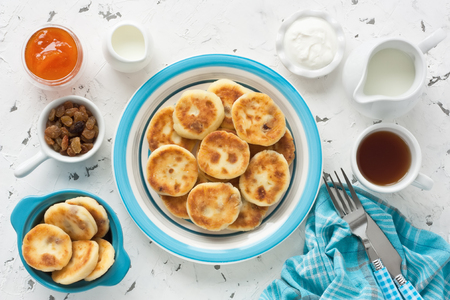 Cottage cheese pancakes with raisin, milk, sour cream, jam and cup tea for breakfast on white rustic background