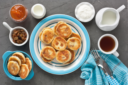 Cottage cheese pancakes with raisin, milk, sour cream, jam and cup tea for breakfast on dark stone rustic background