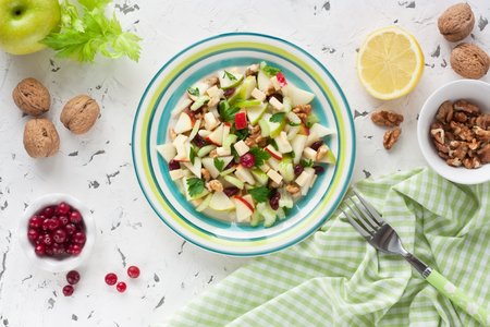 Delicious Waldorf Salad with apple, walnut, celery, cheese and dried cranberries on white rustic background  Stock Photo