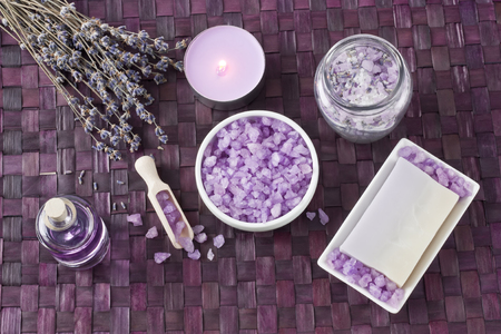Aroma sea salt, aromatic essential oil, natural soap, burning candle and lavender dried flower on bamboo mat Stock Photo