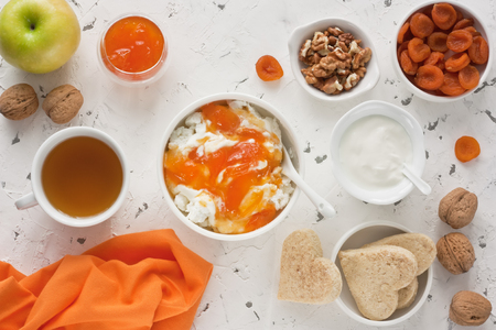 Cottage cheese with apricot jam, sour cream, yogurt, dried apricot, apple, walnut and cup tea with biscuits for healthy breakfast