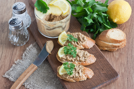 Chicken liver pate with white bread, lemon, parsley on wooden cutting board