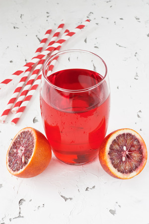 Glass fresh juice drink and red bloody Sicilian oranges on white background