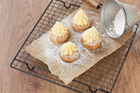 Delicious homemade baked eclair row shells cake with butter cream and sugar powder on metal cooling rack Stock Photo