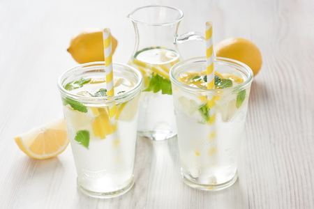 Fresh lemon cold water drink lemonade with mint in two glass