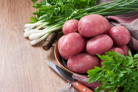 Raw pink potato in copper tray with green onions and parsley on wooden background Stock Photo