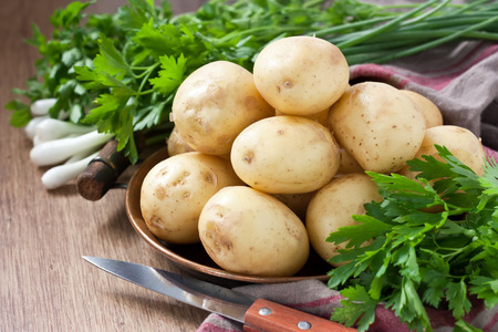 Raw potato in copper tray with green onions and parsley on wooden background Stock Photo