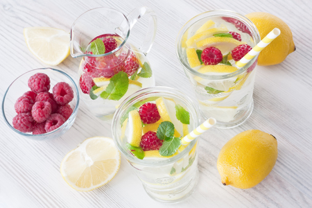 red straw: Fresh lemon and raspberry cold water drink lemonade with mint in two glass Stock Photo