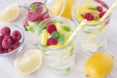 Fresh lemon and raspberry cold water drink lemonade with mint in two glass Stock Photo