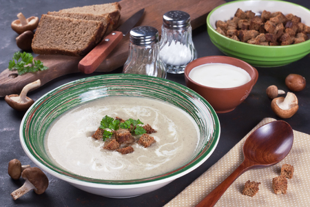 Creamy mushroom soup in bowl with fried croutons, parsley and brown bread on dark background  Stock Photo