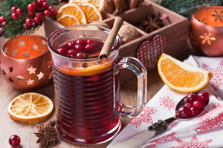 Mulled wine winter hot drink in glass mug with cranberry, cinnamon, dried orange slices, anise star, spices on wooden background