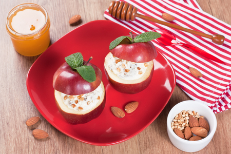Baked apple stuffed cream cheese raisins fried almond slices honey mint in red plate on wooden background Stock Photo