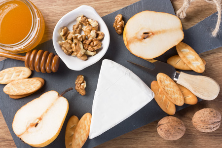 Cheese Brie with halves pear, walnut, honey, crackers on slate board and wooden background  Stock Photo