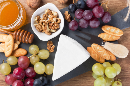 Cheese Brie with grapes, walnut, honey in jar, crackers on slate board and wooden background  Stock Photo