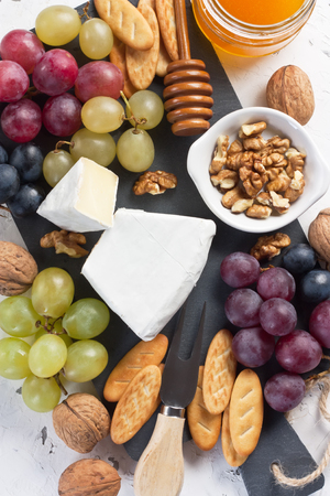 Cheese Brie with honey in jar, grapes, walnut, crackers on slate board and white concrete background