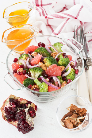 Broccoli, pomegranate, grapefruit salad with walnut, red onion, honey and olive oil in glass bowl on white wooden background