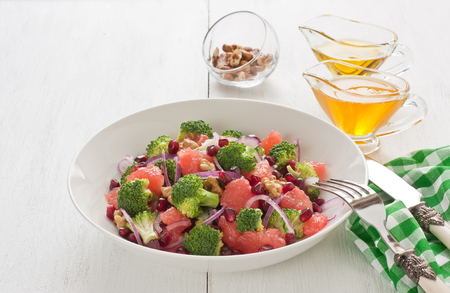 Broccoli, pomegranate, grapefruit salad with walnut, red onion, honey and olive oil in porcelain bowl on white wooden background