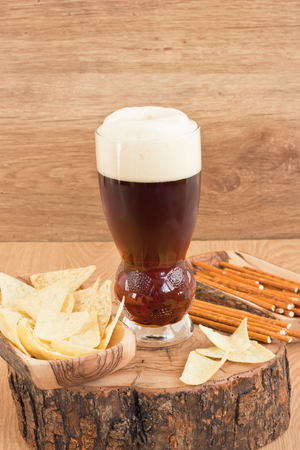 Glass cold dark beer with corn chips and salted straw on wooden background