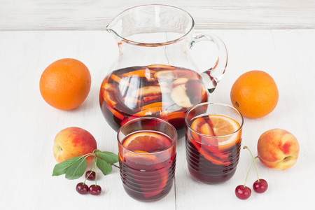 Refreshing red wine sangria in glasses with orange fruit and peach on white wooden background