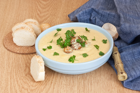 Creamy chanterelle soup in blue bowl with fried mushrooms, parsley and white bread on wooden background