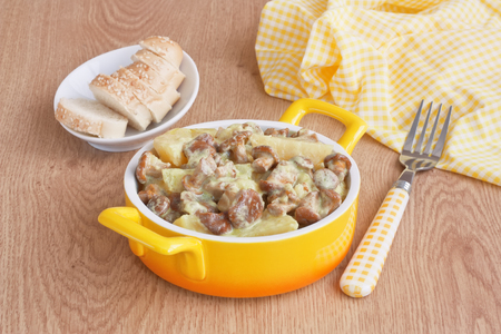 Stewed mushrooms chanterelles with young potatoes in creamy sauce and white bread on wooden background