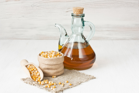 Corn oil in glass pitcher and dried corn kernels on white wooden background