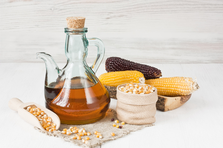 Corn oil in glass pitcher, dry corn kernels and corncobs on white wooden background Standard-Bild