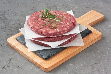 Raw minced beef meat for making burger on slate cutting board and gray concrete stone background