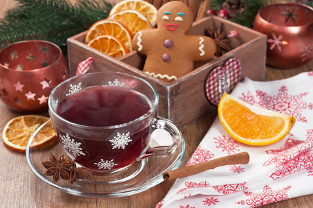 Mulled wine winter hot drink in glass mug with cinnamon, dried orange slices, anise star, spices, gingerbread cookies on wooden background Standard-Bild