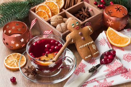 Mulled wine winter hot drink in glass mug with cranberry, cinnamon, dried orange slices, anise star, spices, gingerbread cookies on wooden background