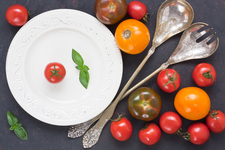 Assortment fresh colorful tomato for salad with white plate, tableware vintage spoon and fork on black rustic background