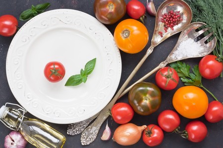 Assortment fresh colorful tomato and vegetable for salad with white plate, tableware vintage spoon and fork on black rustic background