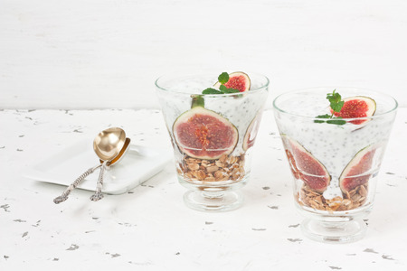 Chia seeds pudding parfait with yogurt, figs, oatmeal granola, and mint in glass on white background