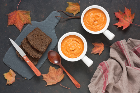 Squash zucchini carrot or pumpkin paste puree with rye bread in white bowl on dark background. Autumn composition with maple leaves