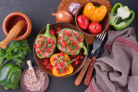 Stuffed colorful bell peppers with rice and minced raw meat, tomato, parsley on rustic dark background