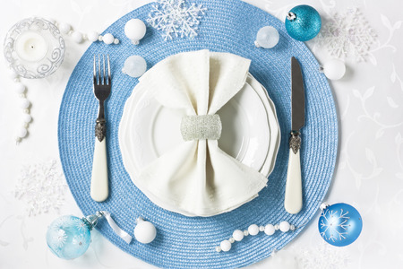 Christmas table setting with decorations, plate, silverware on white table for holiday dinner