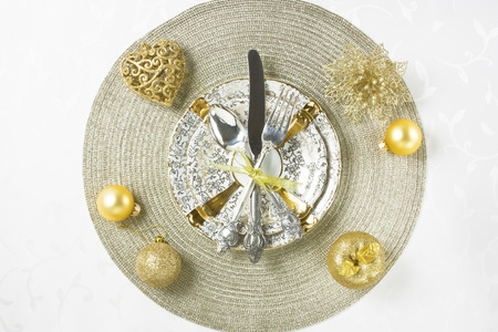 Gold Christmas table setting with decorations, plate, silverware on white table for holiday dinner