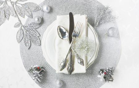 Silver Christmas table setting with decorations, plate, silverware on white table for holiday dinner