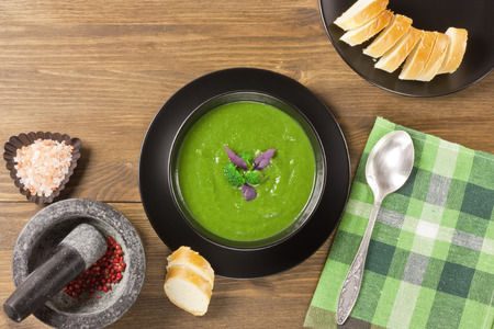 Broccoli creamy soup puree in black bowl with white bread, purple basil leaves, pink salt on wooden background