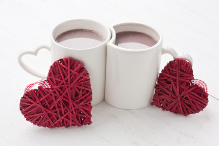 Hot cocoa beverage in white mug decorated red hearts for greeting card on Valentine's Day