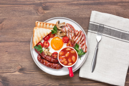 Traditional English breakfast with fried egg, grilled bacon, sausages, beans, mushrooms, cherry tomatoes and toasts in plate on rustic wooden background Standard-Bild