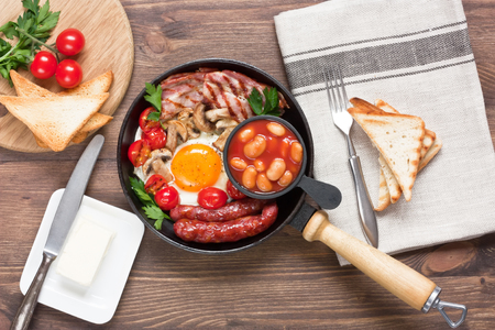 Traditional English breakfast with fried egg, grilled bacon, sausages, beans, mushrooms, cherry tomatoes and toasts in cooking pan on rustic wooden background