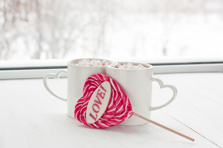 Hot cocoa beverage mug with marshmallow and red heart caramel candy in snow winter day on window background 