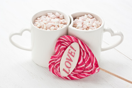 Hot cocoa beverage in mug with marshmallow and red caramel candy in heart shaped on white background