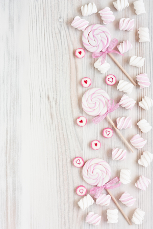 Assorted colored lollipop candy and marshmallow on white wooden background for greeting card. Top view