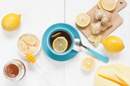 Tea with ginger, lemon and honey in blue cup on white wooden background Standard-Bild