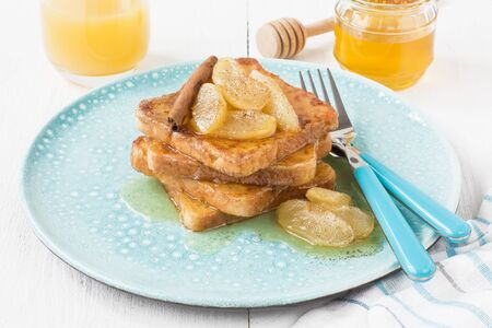 French toasts with caramelized apples, honey and cinnamon for breakfast in blue plate on white wooden background