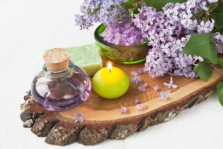 Aroma candle, essential oil, sea salt, natural soap and lilac flower on wooden background