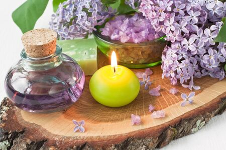 Aromatic candle, essential oil, sea salt, natural soap and lilac flower on wooden background